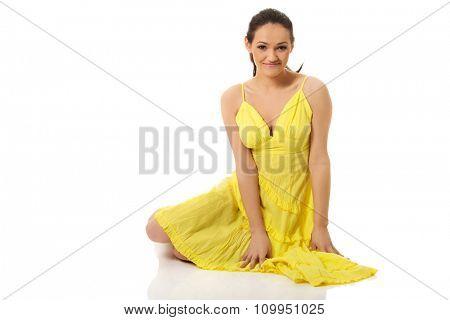 Beautiful woman sitting on the floor in yellow summer dress.