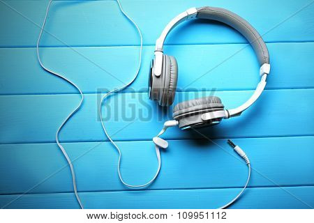 Headphones on blue wooden background