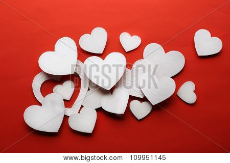 White paper hearts on red background
