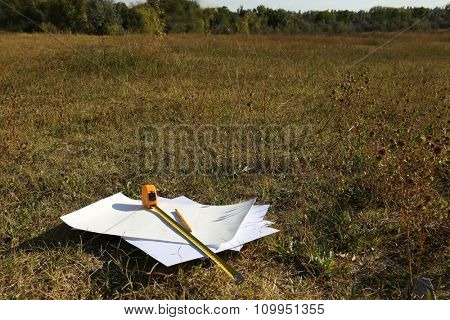 Papers and tape-measure with pencil on the ground in a field