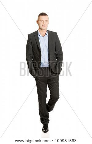 Young smiling businessman with hands in pocket.