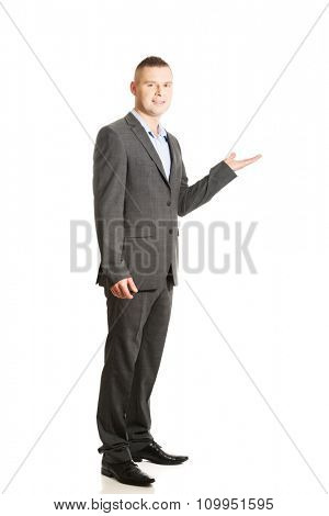 Young smiling businessman holding copyspace.