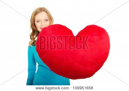Happy teenage woman with heart shaped pillow