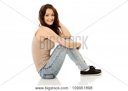 Young smiling student woman sitting on the floor.