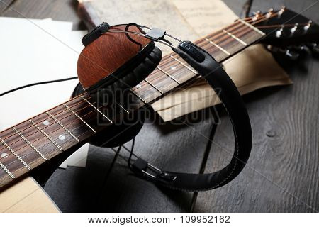 Acoustic guitar, headphones, musical notes and white papers on wooden background, close up