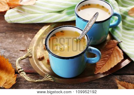 Two mugs of soup on a metal tray