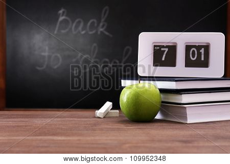 Apple, books and clock on desk background