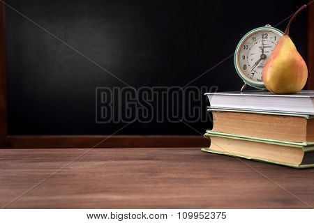 Pear and clock with books on desk background