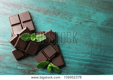 Black chocolate pieces on color wooden background
