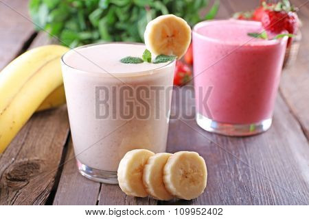 Glasses of fresh cold smoothie with fruit and berries, on wooden background