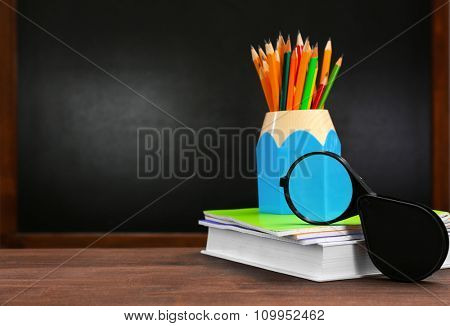 Pencils with book,notebooks and magnifier on desk background