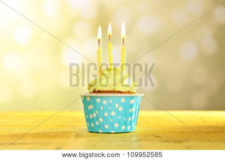 Tasty cupcake with candles on yellow wooden table against unfocused background