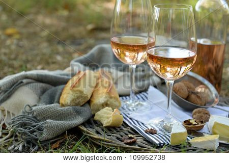 Picnic theme - rose wine, cheese, baguette and nuts on wicker tray, outdoors
