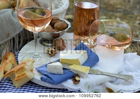 Picnic theme - rose wine, cheese, baguette and nuts outdoors, close up