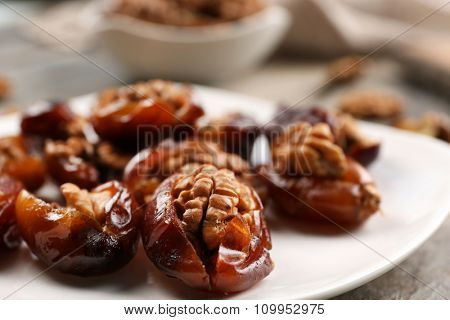 Walnut and date fruit in plate on wooden table, close-up