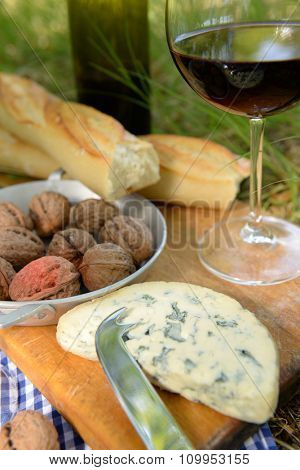 Picnic concept - Wine, delicious cheese, walnuts and baguette on wooden board, close up