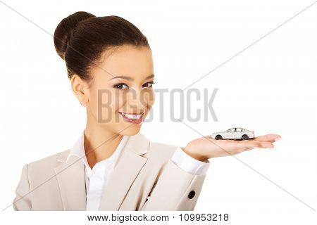 African businesswoman holding small car on palm.