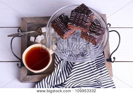 Served table with a cup of tea and chocolate cakes close-up