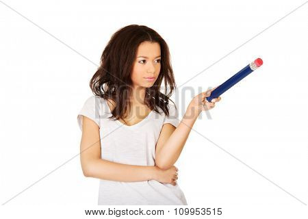 African woman pointing aside with big pencil.