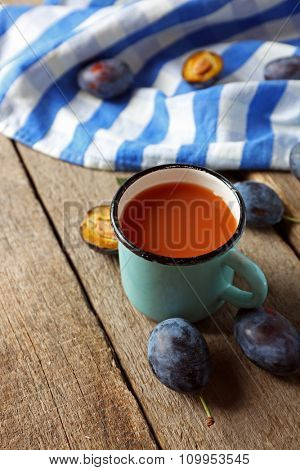Plum Juice in a mug with fresh fruits