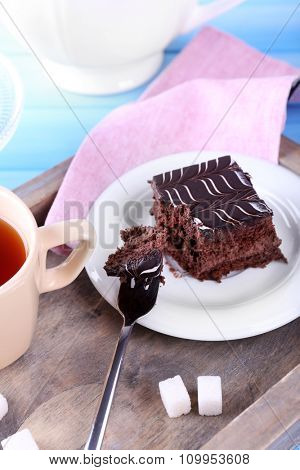 Served table with a cup of tea and chocolate cake on wooden background close-up