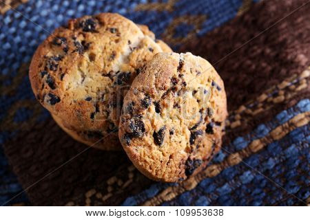 Cookies with chocolate crumbs on ornament napkin against blurred background, close up