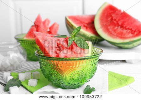 Sliced watermelon in green glass bowl on the table