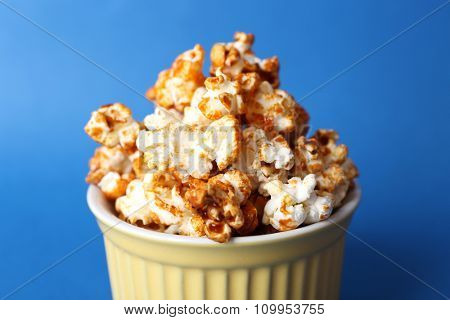 Sweet caramel popcorn on blue background