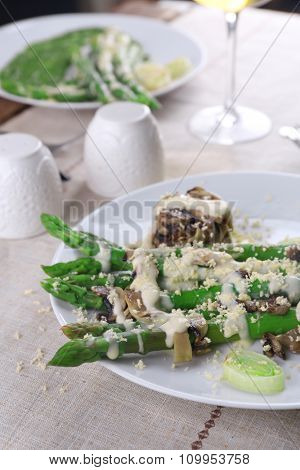 Appetizing dish with asparagus and mushrooms on served table in the restaurant