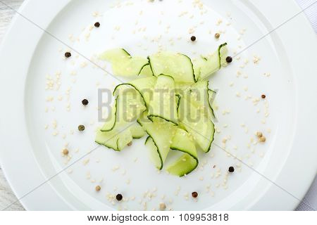 Sliced cucumbers dish on white plate in the restaurant, close up