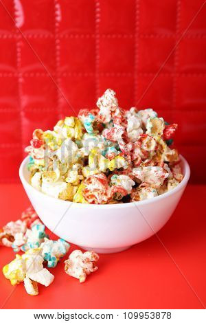 Sweet colourful popcorn on red background