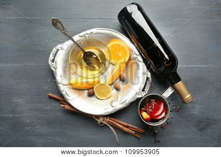 Beautiful composition of traditional mulled wine on decorated grey wooden background