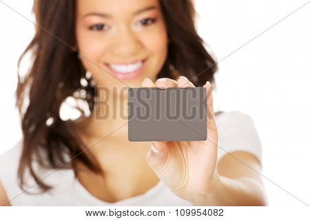 Happy african woman holding a card.