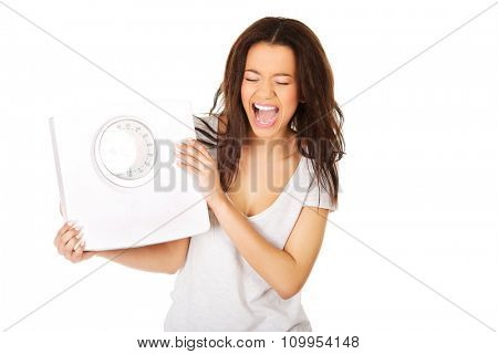 Angry screaming african woman holding a scale.