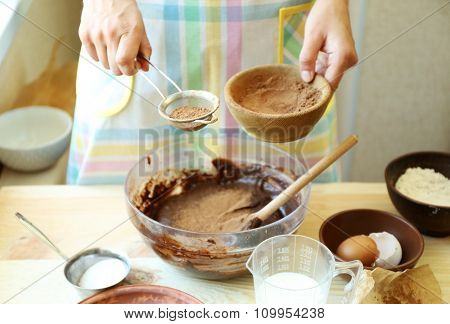 Woman preparing dough for chocolate pie on table close up