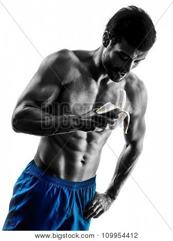 one caucasian man exercising fitness exercises eating Banana in studio silhouette isolated on white background
