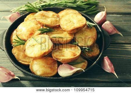Delicious baked potato with rosemary in frying pan on table close up