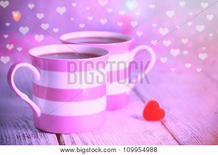 Two cups on table on bright lights background