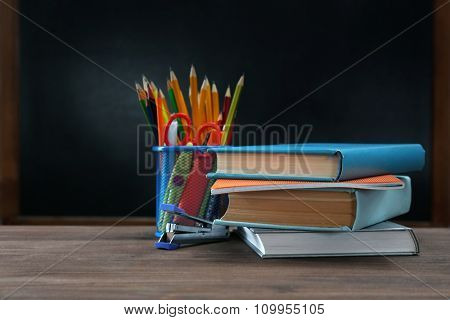Few pencils and books on desk background