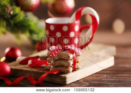 Christmas Candy Canes in cup with Christmas decoration on table on bright background