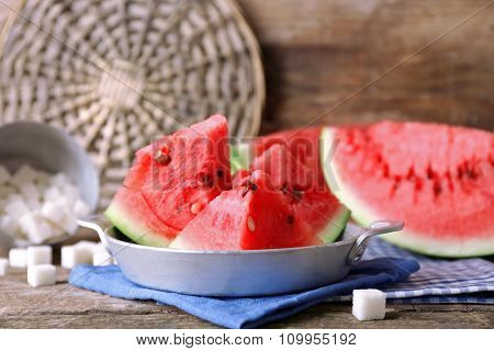 Sliced watermelon in metal bowl on decorated wooden background