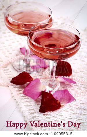 Composition with pink sparkle wine in glasses and rose petals