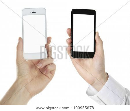 Hands holding black and white smart phones, isolated on white