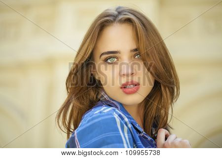 Portrait close up of young beautiful woman in a checkered blue shirt