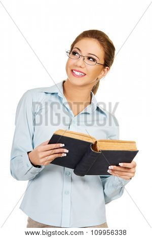 Dreaming business woman holding a book.