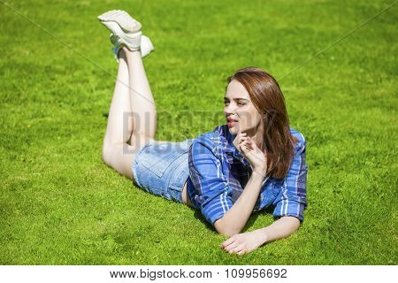 Young beautiful brown haired woman in blue shirt and jeans short lying on green grass