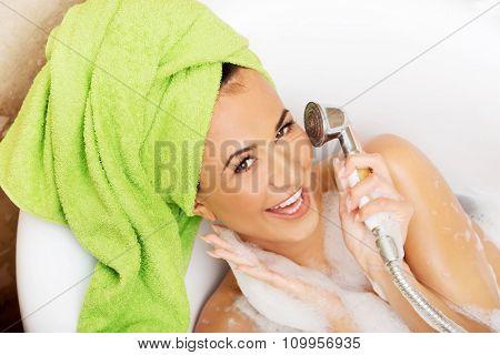 Spa woman having fun with showerhead.