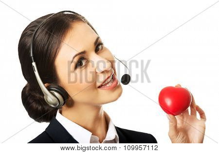 Smiling call center woman holding heart model.