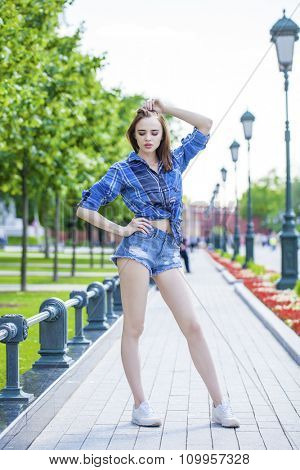 Portrait of young beautiful woman in a checkered blue shirt and jeans short, summer outdoor