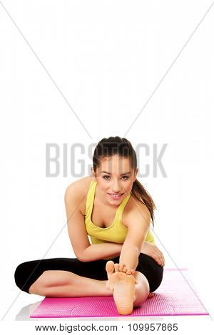 Young fitness woman doing stretching exercise on mat.